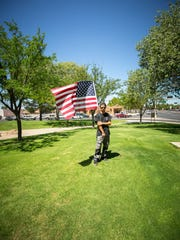 John Bolsins stands with an American flag during a