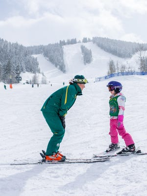 At Utah's Deer Valley, a certified instructor teaches a child to glide through gentle beginner terrain.