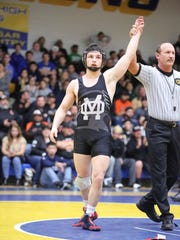 Mission Oak's Jaden Enriquez gets his hand raised by an official after winning a match Saturday at the CIF Central Section Masters Tournament in Clovis. Enriquez won 3-2 to capture the section title at 138 pounds.