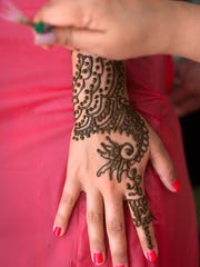 Juli Raymond, of O'Fallon, Mo., receives a henna tattoo from Fort Myers resident Shelly Maniktala at the Naples India Fest at Fleischmann Park on Saturday, March 19, 2016, in Naples.