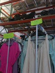 A rack of clothing sits in front of heavy machinery