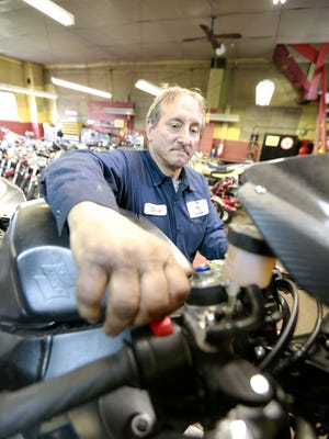 Steve Kasten works on a cycle at his shop, S-K Service in Hatley.