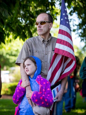 John Strohmeyer and daughter Tamar, 8, of Colfax, watch the posting of the colors at a Memorial Day multi-war service at the Iowa State Capitol grounds Monday May 29, 2017, in Des Moines, Iowa. Wreaths were laid at Korean, Vietnam and Irag/Afghanistan memorials.