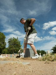 Joel Craig cleans up around grave markers at the San