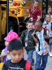 Students arrive by bus on the first day of school at