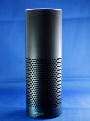 """FILE - This July 29, 2015 file photo made in New York shows Amazon's Echo, a digital assistant that continually listens for commands such as for a song, a sports score or the weather. The company says Echo transmits nothing to Amazon's data centers until you first say """"Alexa"""" or press a button. A blue light also comes on to let you know it's active."""