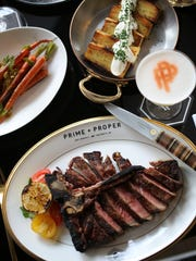 A spread of dishes and a cocktail from Prime + Proper,
