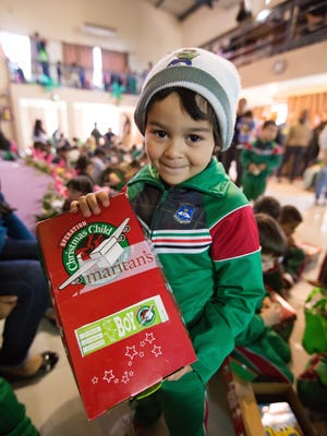 A child receives an Operation Christmas Child shoe box during distribution at Heaven's Kingdom Christian School in San Lorenzo, Paraguay.