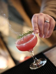 Food and beverage director Dustin Walker puts the finishing touch — a sprig of torched rosemary — onto his Touch of Grey cocktail ($12) at Red Dunn Kitchen in Corktown.