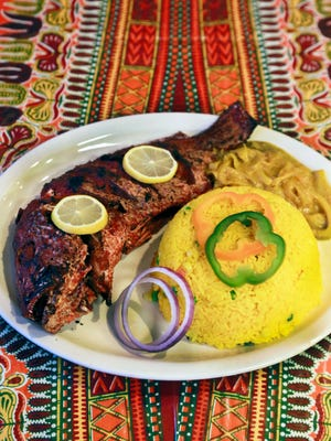 Whole grilled red snapper with rice and yassa, a Senegalese onion sauce, from Maty's African Cuisine in Detroit.
