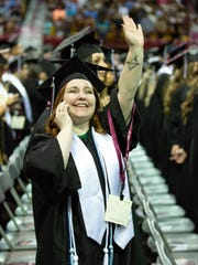 New Mexico State University graduate Karen Carson waves to her loved ones on Saturday, May 12, 2018, during NMSU's commencement at the Pan American Center.