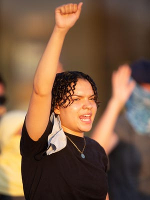 Sierra Jackson, 18, puts her fist in the air while chanting along with protesters earlier this month in front of Target at S.W. 29th and Wanamaker.
