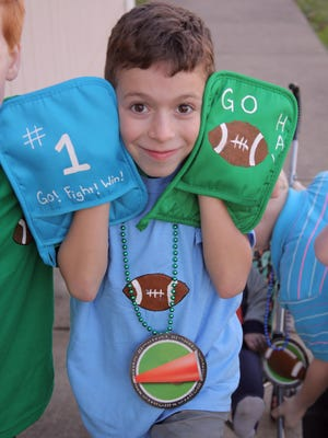 Cavan Quinones, age 8, shows off his football oven mitt signs, T-shirt and medallion.