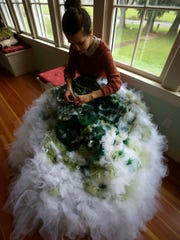Kate Miles, 15, works on a shamrock dress at her home
