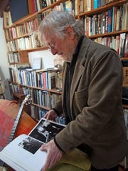 John Cohen, a legendary musician and rock photographer, looks through some of his published work at his home in Putnam Valley. He and others are working to acquire the Tompkins Corners Methodist Church to turn it into a nonprofit cultural center.