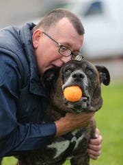 Pete Buchmann, 54, gives his 9-year-old dog, Buster, a hug while playing with him outside of Faithful Friends in 2014.