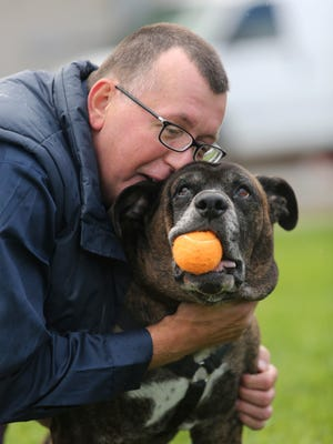 Pete Buchmann, 54, gives his 9 year-old dog Buster, a hug while plain with him outside of Faithful Friends.