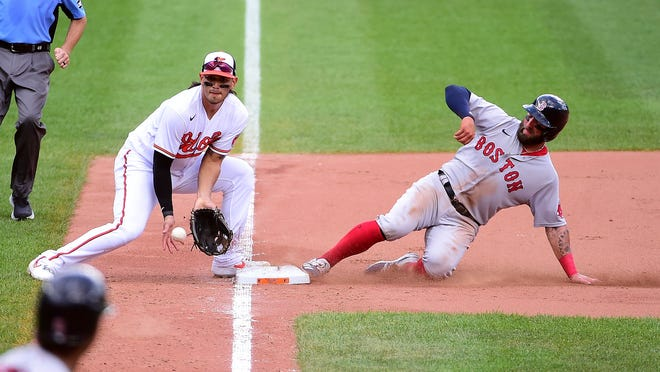 Boston's Kevin Pillar, right, slides safely with a steal of third base during Sunday's sixth inning against the Orioles.