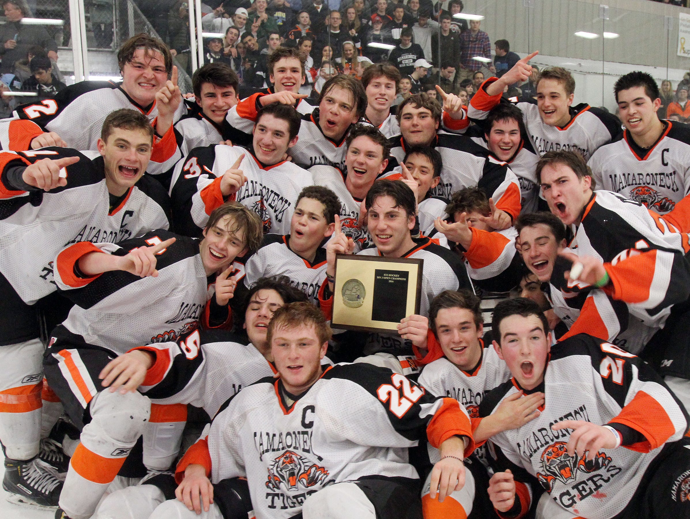 Mamaroneck players celebrate with the Section 1 championship plaque after defeating Suffern 5-1 at The Brewster Sports Arena Feb. 26, 2016.