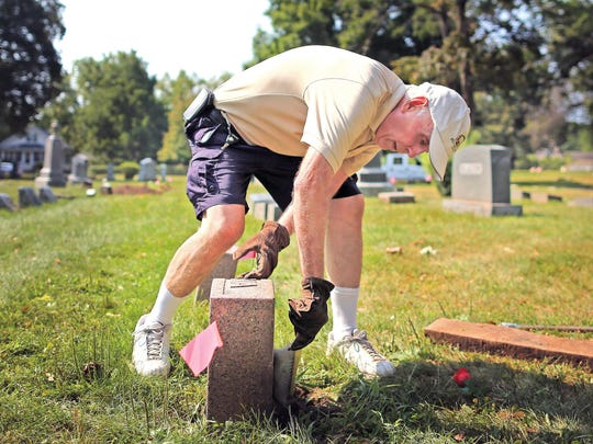John Kalkirtz brushes off a grave marker after uprighting it while at Oakwood Cemetery in Beloit, Wis. Kalkirtz has volunteered for the last two years to help preserve fallen and broken grave markers at Oakwood and Eastlawn cemeteries, restoring more than 50 grave markers.