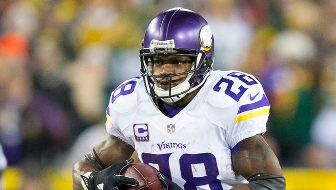Minnesota Vikings running back Adrian Peterson (28) rushes with the football during the second quarter against the Minnesota Vikings at Lambeau Field.