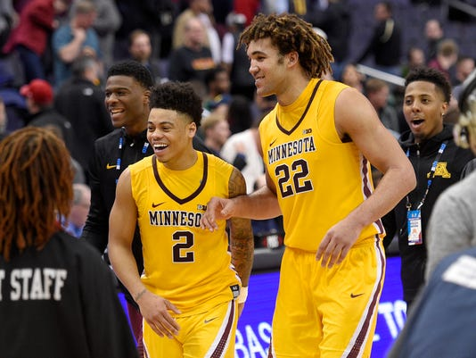 Minnesota center Reggie Lynch (22) and guard Nate Mason (2) react as they leave the court after an NCAA college basketball game against Michigan State in the Big Ten tournament, Friday, March 10, 2017, in Washington. Minnesota won 63-58. (AP Photo/Nick Wass)