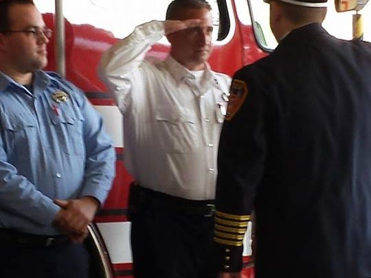 Arlington Fire District Lt. Michael Bohack is saluted by fire Chief Tory Gallante, while firefighter Christopher Mills looks on, for their role in saving the life of a newborn baby boy.