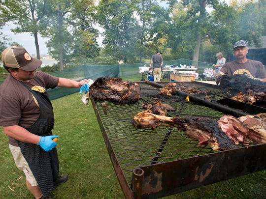 Master Butcher Frank Pace of The Guild Commissary pulls a section of steer off a custom-made grill after it had been cooking overnight at the Eat by Northeast food festival at Oakledge Park in Burlington on Sunday.