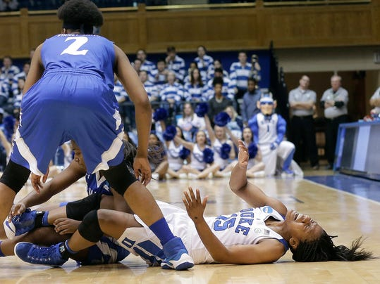 Duke's Kyra Lambert (15) grimaces due to an injury while chasing the ball with Hampton's Monnazjea Finney-Smith (2) during the first half of a first-round game in the NCAA women's college basketball tournament in Durham, N.C., Saturday, March 18, 2017. Duke won 94-31. (AP Photo/Gerry Broome)