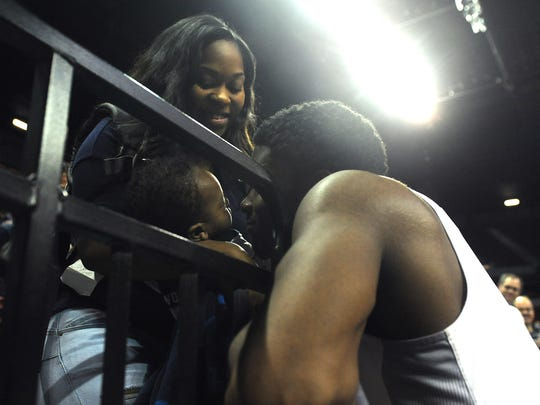 Cameron Oliver kisses his son as his girlfriend looks on after Nevada beat Utah State in the Mountain West Tournament. All three will be in Brooklyn for the NBA draft.