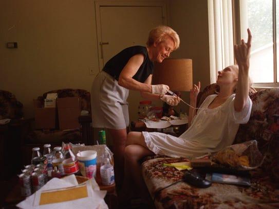 A nurse cleanses Loretta's chest tube during a visit