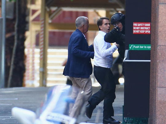 Two hostages run to safety outside the Lindt Cafe,