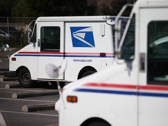 U.S. Postal Service mail vehicles sit in a parking