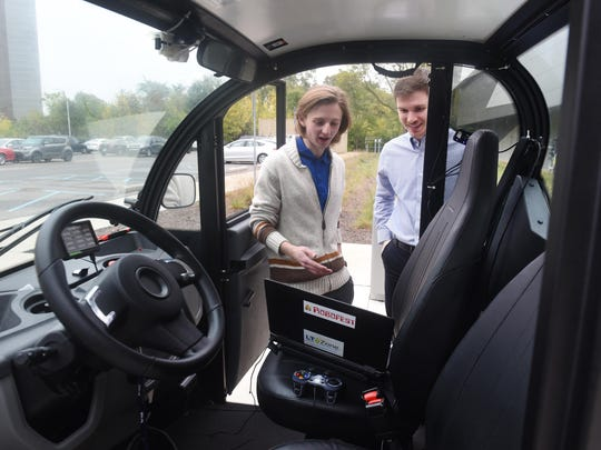 Lawrence Technological students Nicholas Paul and Gordon Stein run programs on Thursday for a autonomous campus transport designed at the Southfield center.