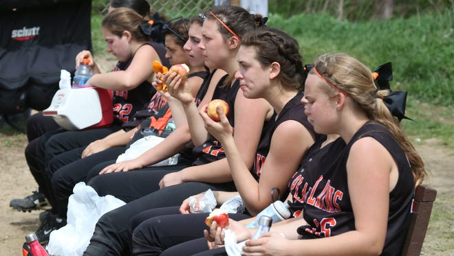 The White Plains softball team sneak in snack time as they wait to play Saunders in the championship game of the 1st annual Pete Dronzek Memorial Softball Tournament at Sullivan's Oval in Yonkers, April 29, 2017.