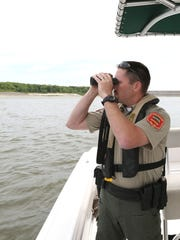 Dustin Eighmy, a conservation officer with the Iowa DNR, patrols watercraft on Saylorville Lake on Saturday, May 23, 2015.