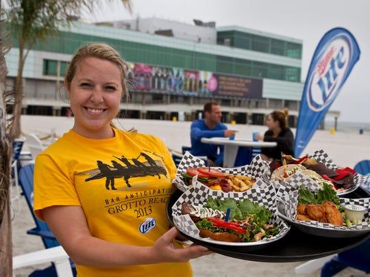 Cocktail waitress Sara Joyal delivers food to patrons at the Bar Anticipation Beach Bar at the Trump Plaza in Atlantic City.