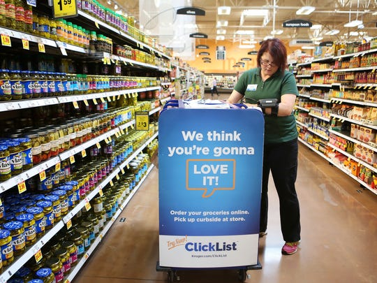 Kroger employee Shar Libby grabs items to fill a digital
