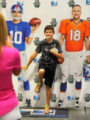 Trenton Conyer, 11, poses with a poster of Eli and Peyton Manning at the Music City Sports Festival on Saturday at Music City Center.