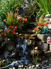 Whimsical ornaments and moisture loving plants such as Sarracenia accent the cascading waterfall.