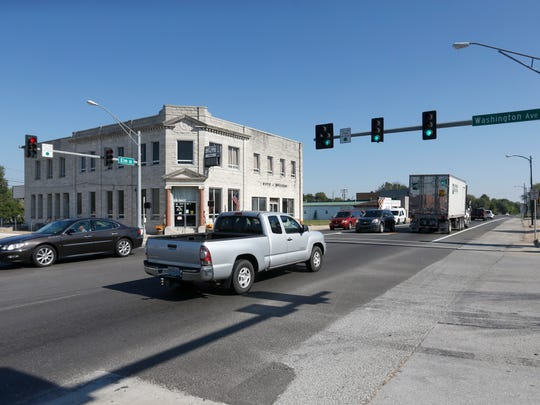Vehicles drive along the wide roads in front of Billings City Hall at the intersection of Elm Street and Washington Avenue.