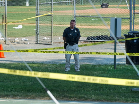 A police officer stands watch behind police tape near strewn baseballs on a field in Alexandria, Va., Wednesday, June 14, 2017, after a multiple shooting involving House Majority Whip Steve Scalise of La.