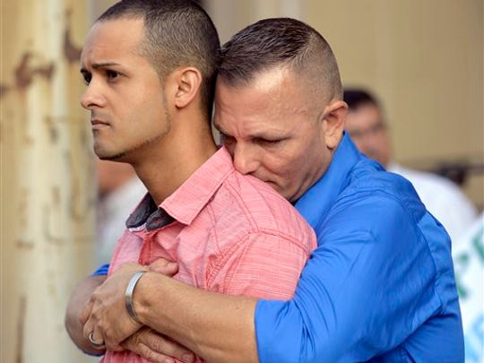 Jonathan Beebe-Franqui, left, and his husband Dwayne D. Beebe-Franqui embrace as they wait for the arrival of Rowan County Clerk Kim Davis at the Carl D. Perkins Federal Building in Ashland, Ky., Thursday, Sept. 3, 2015. Davis has been ordered to appear in Federal Court to explain why she is refusing to issue marriage licenses despite a federal order to do so.