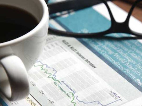 Paperwork showing bar graphs sits underneath a cup of coffee and readers.