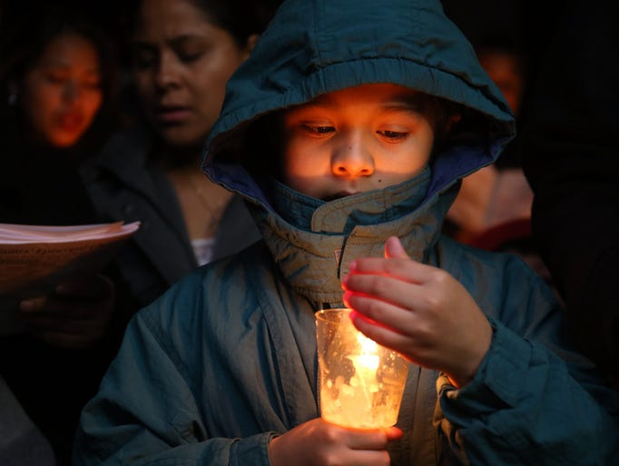 Eight-year-old Alonso Vidal holds a candle during the