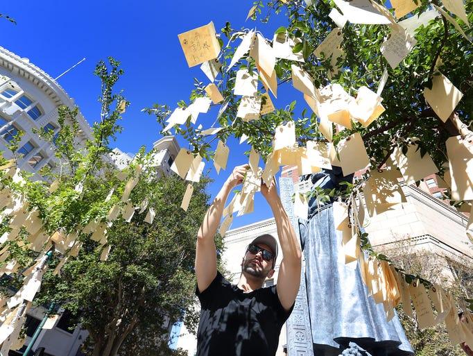 Tony Diaz attaches his dream to the Dream Tree at Chalk