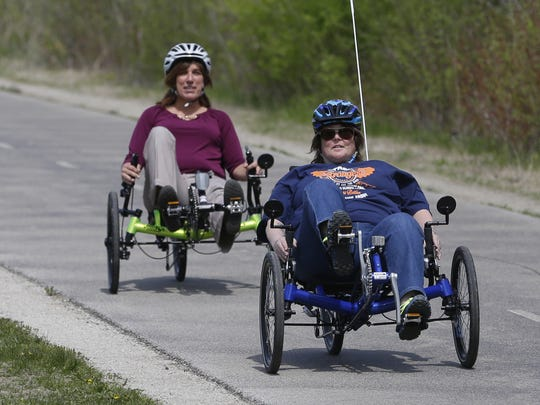 Debra Sanchez, left, Bellin Health Stroke Support Group coordinator, rides a special recumbent bike with stroke survivor Michelle Nelson of Little Suamico along the Fox River Trail on Monday, May 9,  2016.