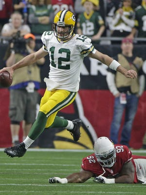 Green Bay Packers quarterback Aaron Rodgers (12) leaps away from a tackled attempt by Arizona Cardinals defensive end Frostee Rucker (92) at University of Phoenix Stadium.