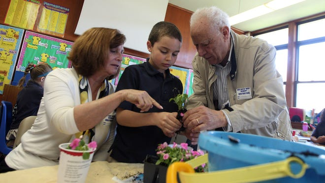 Evan Guirgus helps his grandparents, Barbara and Edward Guirgus, on Wednesday at Our Lady of Mercy Academy during Grandparents Day.