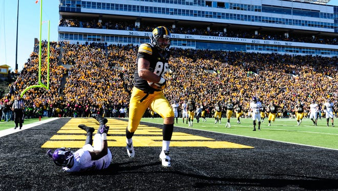 Iowa Hawkeyes tight end C.J. Fiedorowicz (86) makes an eight-yard touchdown reception as Northwestern Wildcats safety Traveon Henry (10) defends in overtime at Kinnick Stadium. Iowa won 17-10.